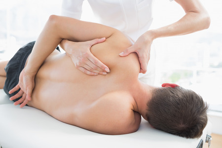 adult massage: Professional female physiotherapist giving shoulder massage to man in hospital