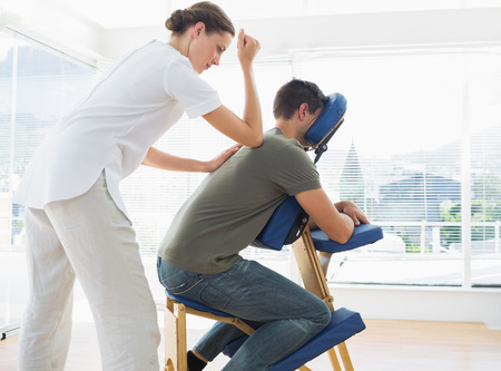 chair massage: Side view of man receiving massage from physiotherapist in hospital