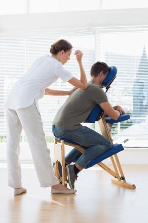 masoterapia: Longitud total de terapeuta mujer dando vuelta masaje al hombre en el hospital