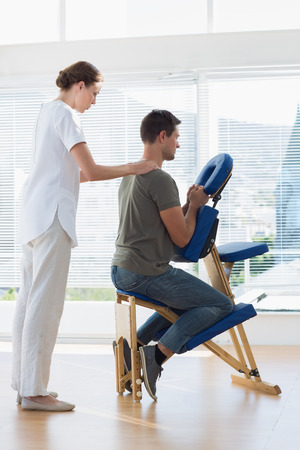 Full length of female physiotherapist massaging man on massage chair in hospital photo
