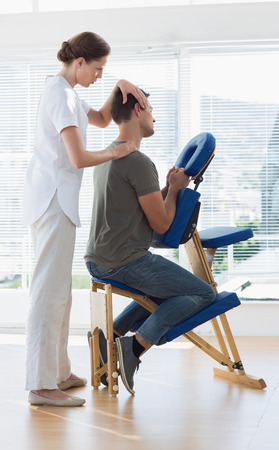 chair massage: Full length of massage therapist massaging man in hospital
