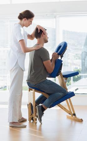 Full length of massage therapist massaging man in hospital