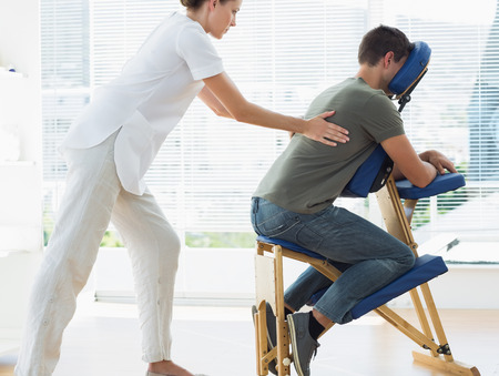 Side view of female therapist massaging man in hospital photo