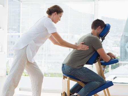 Zijaanzicht van de mens die rug massage van fysiotherapeut in het ziekenhuis Stockfoto