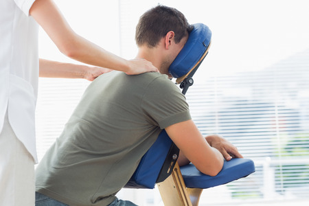 Female physiotherapist giving shoulder massage to man on massage chair in hospital