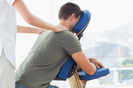 masaje: Fisioterapeuta sexo femenino que da masaje del hombro a hombre en silla de masajes en el hospital