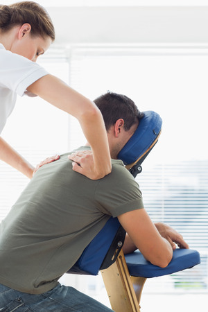 massage therapy: Man receiving back massage from female therapist in hospital