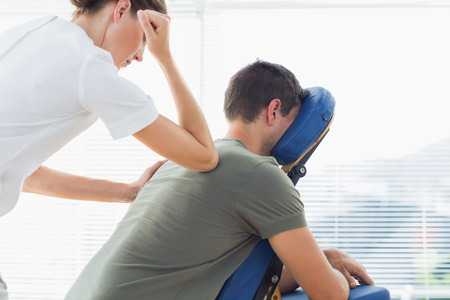 massage chair: Female therapist giving back massage to man in hospital