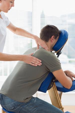 Therapist massaging man on massage chair in hospital