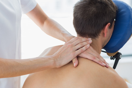 Rear view of man receiving shoulder massage by female therapist in hospital photo