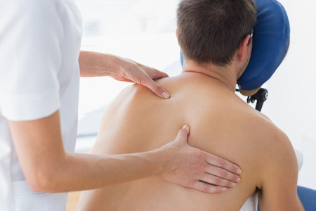 Rear view of male patient being massaged by female therapist in hospital