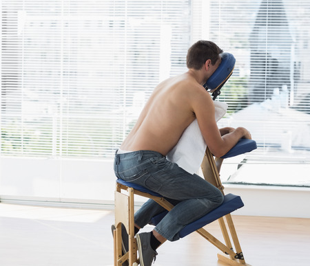 Shirtless male patient sitting on massage chair in hospital