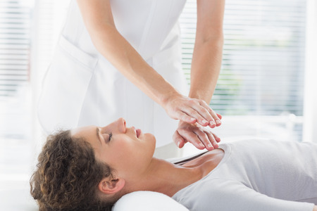 female therapist: Female therapist performing Reiki over woman at health spa Stock Photo