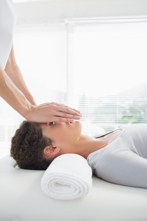 Beautiful young woman having reiki treatment over face in health spa photo