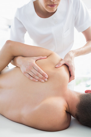 Professional female therapist giving shoulder massage to man in hospital Stock Photo