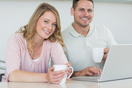 Portrait of happy couple with coffee mugs and laptop at table in kitchen photo