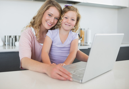 Portrait of mother and daughter with laptop sitting at table in kitchen photo