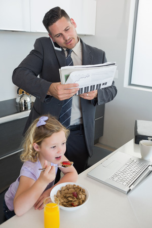Businessman with mobile phone and newspaper standing by daughter having breakfast at home photo