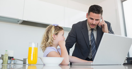 Daughter looking at father on call using laptop at table in house photo