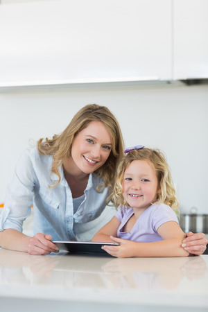 Smiling mother and daughter with digital tablet in kitchen photo