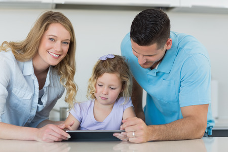 Mother and father assisting daughter in using digital tablet at table photo