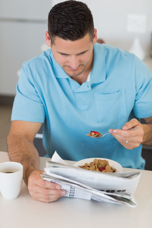 eating breakfast: Man reading newspaper while eating breakfast at table in kitchen