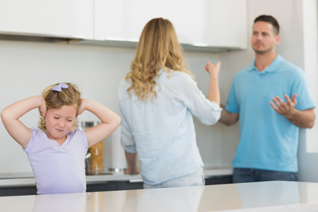 Frustrated little girl covering ears while parents arguing in kitchen photo