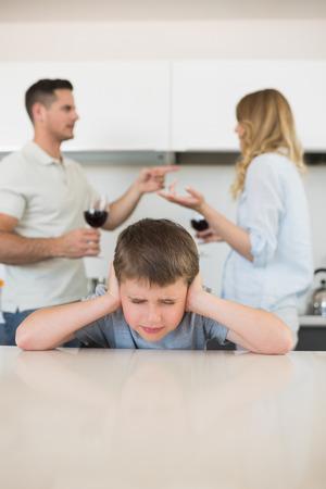 pareja discutiendo: Chico irritado cubre orejas mientras los padres discutiendo en segundo plano en el hogar Foto de archivo