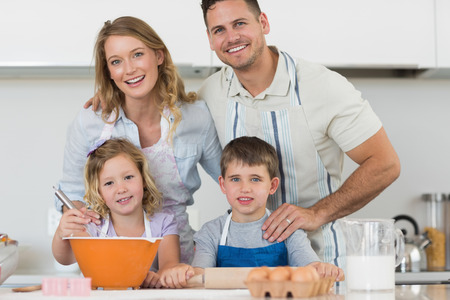 Portrait of happy family baking cookies together at kitchen counter photo