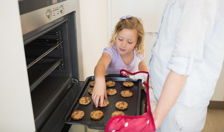 Girl positioning cookie on baking sheet while mother holding it in kitchen photo