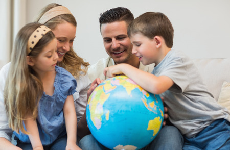 Happy family of four searching places on globe in house photo