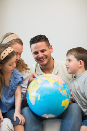 Happy family eploring places on globe in house photo