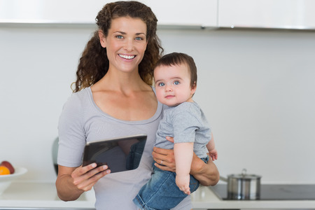 Portrait of happy mother carrying baby boy while holding digital tablet in kitchen at home photo