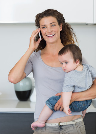 Happy woman answering smartphone while carrying baby boy in kitchen photo