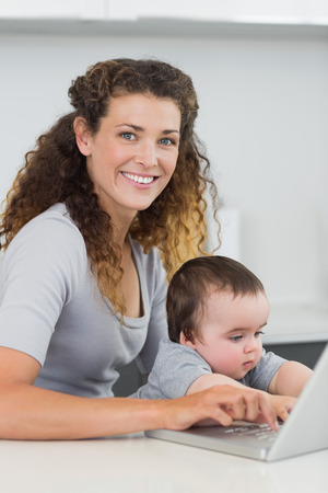 Portrait of beautiful woman with baby boy using laptop at counter photo