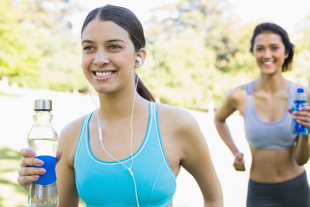 Smiling young fit women with water bottle listening music while jogging in park photo