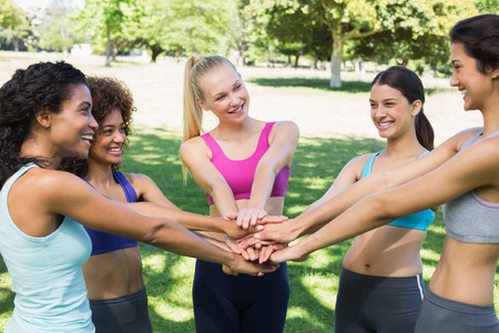 Fit young female friends stacking hands in the park Stock Photo
