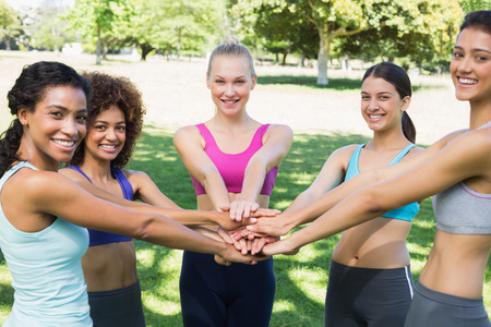 Portrait of happy fit young female friends stacking hands in the park