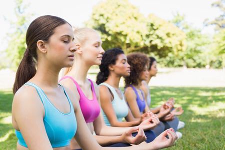 Female friends meditating in lotus position at the park photo