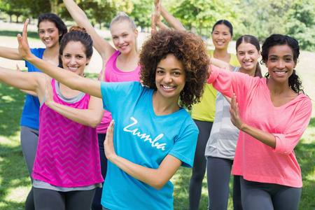 zumba: Portrait of multiethnic friends performing Zumba dance in park Stock Photo