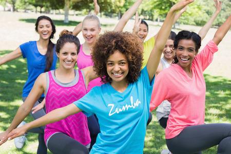 Portrét usmívající se ženy vykonávajících fitness tanec v parku