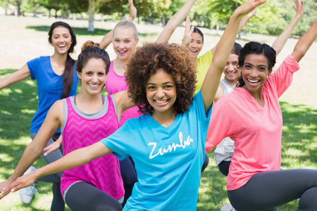 lifestyle outdoors: Portrait of smiling women performing fitness dance in park