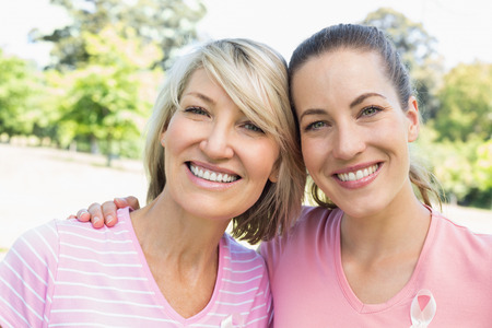 Portrait of confident female volunteers participating in breast cancer awareness at park