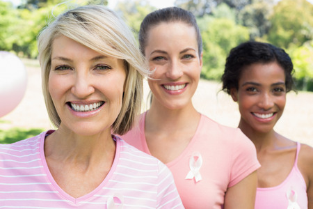 Portrait of confident female volunteers participating in breast cancer awareness photo