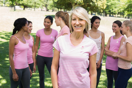 Portrait of confident woman supporting breast cancer awareness with friends in background at park photo
