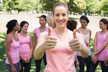 Portrait of female volunteer gesturing thumbs up at breast cancer campaign in park photo