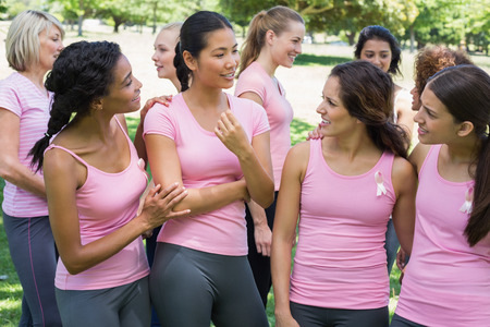 Female volunteers discussing during breast cancer awareness at park photo