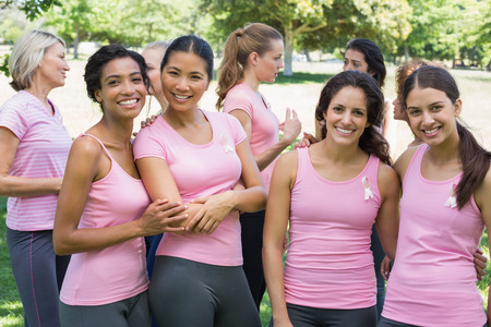 Portrait of smiling female volunteers participating in breast cancer awareness at park photo