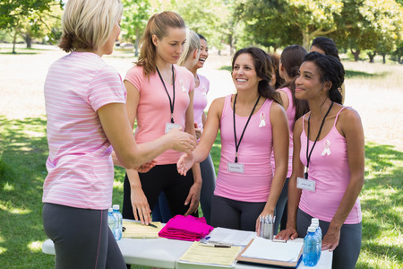 Happy female volunteer shaking hands with participants during breast cancer awareness in park photo