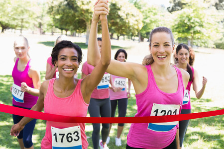 Portrait of happy female breast cancer participants crossing finish line at marathon race in park photo
